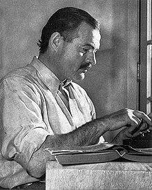 Dark-haired man in light colored short-sleeved shirt working on a typewriter at a table on which sits an open book