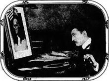 Barrymore sitting at a desk in profile, looking at a picture of George Washington