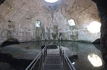 Bare concrete dome interior today called the Temple of Mercury with two square windows halfway up the dome on the far side, a circular oculus at the top, and a water level that reaches up to the base of the dome