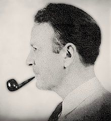 Man with slicked-back black hair facing left, smoking a pipe