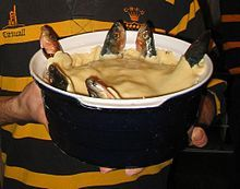A blue ceramic dish containing a stargazy pie, with six fish poking out of a shortcrust pastry lid, looking skywards