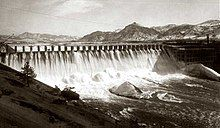 Front view of a dam releasing water through its spillways