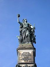 Monument of robed woman, standing, holding a crown in one hand and a partly sheathed sword in another
