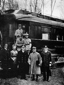 black and white photograph of five men in military uniforms standing side-to-m right, seen outside his railway carriage No. 2419D in the Forest of Compiègne.