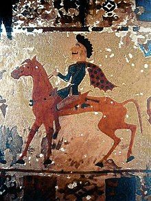 This picture is of a Pazyryk man riding a red horse shown in profile view. The man has black hair and is wearing a flowing red and blue polka dotted cape.