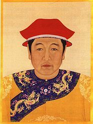 A painted image of the head and chest of a black-haired man with droopy eyes wearing a white-edged two-tiered red cap and a bright yellow garment whose lapels are decorated with five-clawed yellow dragons against a blue background with clouds and vegetation.