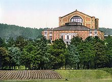A building stands beyond a part-ploughed field and a row of trees. It has five sections. Farthest away, the tallest part with a v-shaped roof contains the stage. Adjoining it is the auditorium section built of patterned brick. Nearest is the royal entrance, made of stone and brick with arched windows and a portico. Two wings adjoin the auditorium.