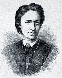 A middle-aged woman with shoulder-length black hair looking to her left dressed in a high-necked shirt and a large cross on a chain
