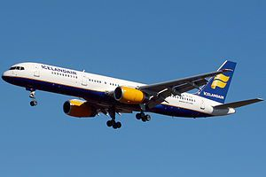 A mostly white Boeing 757 with blue and yellow trim preparing for landing against a blue sky. Landing gear and flaps are fully extended in final approach configuration.