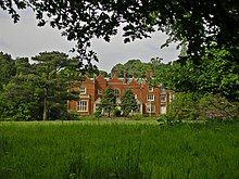 Colour photograph of a large country house in parkland