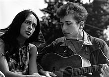 Dylan is seated, singing and playing guitar. Seated to his right is a woman gazing upwards and singing with him.