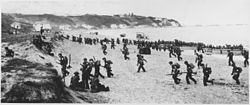 """Near Algiers, """"Torch"""" troops hit the beaches behind a large American flag """"Left"""" hoping for the French Army not fire... - NARA - 195516.jpg"""