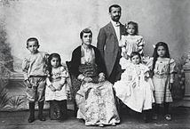 Photograph of Pontic Greek man, woman, and their children. The man is dressed in Western clothes, the woman in traditional costume.