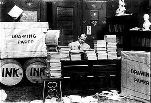 McCay seated at center, surrounded by massive stacks of paper and barrels of ink