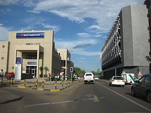 A road with a Bank Gaborone building to the left and a taller building with curved truss structures on the windows to the right