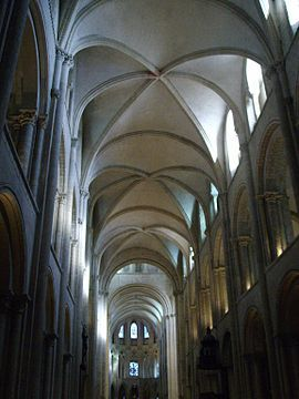 A tall wide church of grey stone, elegantly vaulted with fine ribs.