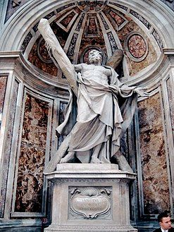 This statue shows an elderly man, bare-chested, and draped, looking up despairingly as he supports a large cross, arranged diagonally.