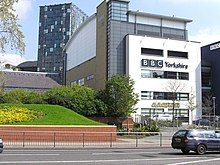 """A quirky modern five-storey building with a large sign saying """"BBC Yorkshire"""" in black above the second-floor windows on the white-fronted façade of the lower four floors can be seen on the far side of a dual-carriageway road with a barrier along the central reservation. At right-angles to the right of the building is a tall blue slab with the letters """"BBC"""" in white at the top. The left side of the building is mostly brick-red with a few windows, but above it is a light blue windowless section. The roof above this and the grey fifth floor of the frontage curves gently down to the rear. A lone car is driving from left to right along the road; between it and the building, temporary boards have been erected in front of a building to the left. In the top left-hand corner of the picture, part of a tall many-windowed building can be seen."""