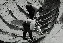 Black and white photograph showing two excavators working in the ship impression at Sutton Hoo