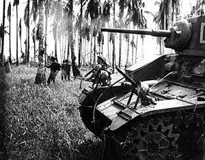 7 January 1943. Australian forces attack Japanese positions near Buna. Members of the 2/12th Infantry Battalion advance as Stuart tanks from the 2/6th Armoured Regiment attack Japanese pillboxes. An upward-firing machine gun on the tank sprays treetops to clear them of snipers. (Photographer: George Silk).
