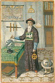 Color print of a man with a long white beard wearing a double-edged round cap and dressed in a long robe, who is pointing a compass to a celestial globe that is sitting on a table on the left.
