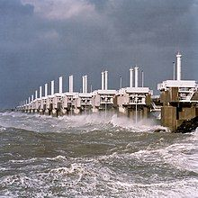 A long row of concrete towers with steel structures connecting them and a very rough sea