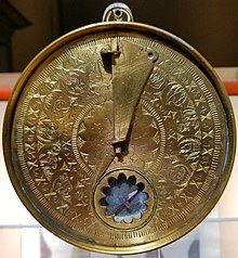Circular brass time measurement device with engraved Arabic toponyms and zodiac symbols.