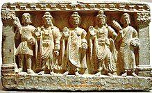stone statue group, a Buddhist triad depicting, left to right, a Kushan, the future buddha Maitreya, Gautama Buddha, the bodhisattva Avalokiteśvara, and a Buddhist monk. 2nd–3rd century. Guimet Museum