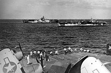Black and white photo of two aircraft carriers sailing in close formation viewed from the flight deck of another aircraft carrier
