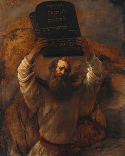 This is an image of an oil on canvas picture by Rembrandt (1659) of a bearded man representing Moses with two tablets of stone of the ten commandments held high in both hands.