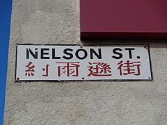 A sign reading Nelson Street, with text in Chinese underneath.