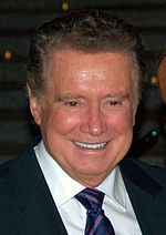 A man wearing a black suit including a white shirt and blue/purple tie.
