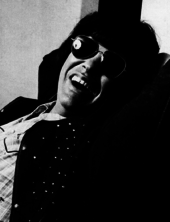A dark-haired man wearing dark glasses and grinning broadly