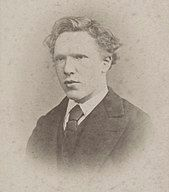 Head shot photo of the artist as a clean-shaven young man. He has thick, ill-kept, wavy hair, a high forehead, and deep-set eyes with a wary, watchful expression.