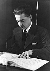young clean-shaven man, with dark, slicked back hair; he is studying a musical score