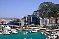 Yachts and boats anchored in a marina that lined with jetties and modern apartment blocks, with the Rock of Gibraltar in the background