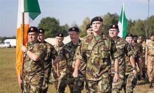 Male and female soldiers wearing camouflage marching behind the Irish tri-color flag.