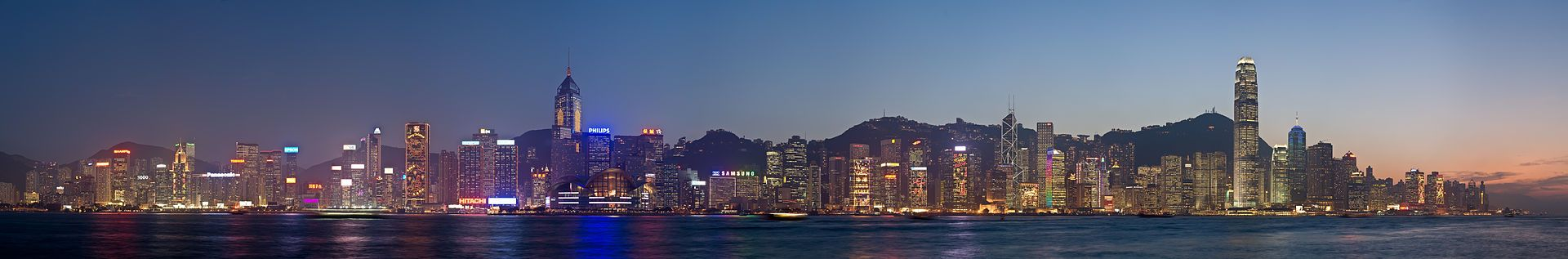 Night time city skyline with Victoria Harbour in front and low hills behind