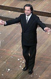 man with dark, centre-parted collar-length hair