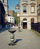 """Two ornate metal pillars with large dishes on top in a paved street, with an eighteenth-century stone building behind, upon which can be seen the words """"Tea Blenders Estabklishec 177-"""". People sitting at café-style tables outside. On the right are iron railings."""