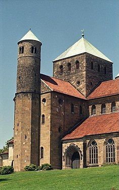 The exterior of the same church shows a short square tower with a pointed metal roof over the crossing, and a small round tower at the end of the transept.