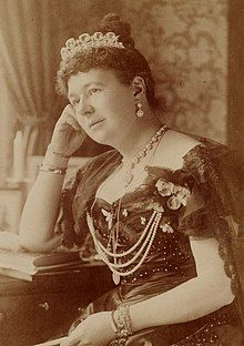 A sepia-toned, formal photograph of a seated, bejewelled woman