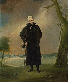 White-haired man stands outdoors beside a tree with cane.