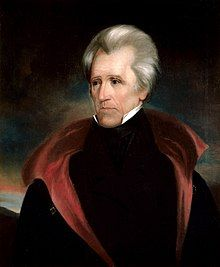 A portrait of Andrew Jackson, serious in posture and expression, with a grey-and-white haired widow's peak, wearing a red-collared black cape.
