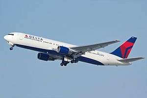 A side/underneath view of a Boeing 767-300 in Delta Air Lines' white, blue, and red color during climbout. The main undercarriage doors are retracting.
