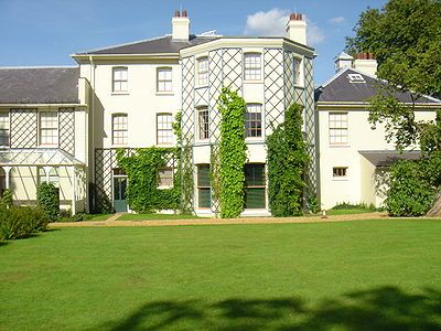 Stucco rendered building in a plain Georgian style with hipped slate roofs and overhanging eaves. The central block is three storeys, and there are two-storey extensions on each side. Lattices are fixed to walls between windows to support climbing plants. A wide lawn forms the foreground, and tall trees appear behind the block to the right.