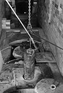 铁链吊着一根柱形容器,容器一部分已没入下方的设备中。