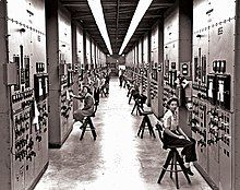 A long hallway, with bulky computers reaching from the floor to the ceiling, covered in switches and dials. Women sit on chairs operating the machinery.