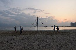 A young people is playing volleyball in beach.jpg