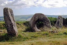 two weathered stones standing at an angle on a grassy hill, with a third doughnut-shaped stone between them